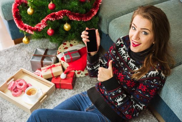 Mujer sonriente joven que sostiene el teléfono y que muestra el pulgar para arriba en navidad