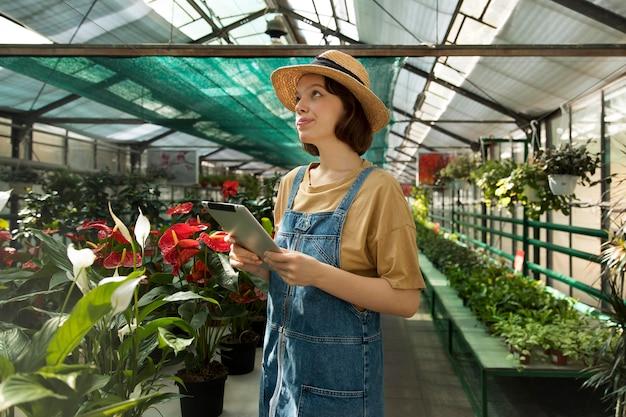 Mujer sonriente joven que trabaja en un invernadero