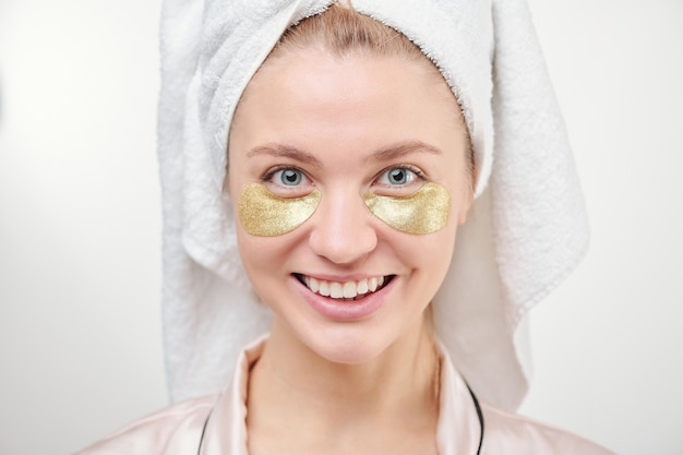 Mujer sonriente joven sana con revitalizantes parches dorados debajo de los ojos de pie en aislamiento