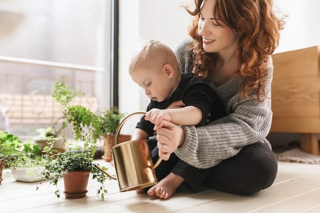 Mujer sonriente joven sentada en el piso con su pequeño hijo guapo sosteniendo regadera en manos con plantas verdes alrededor de ventana grande