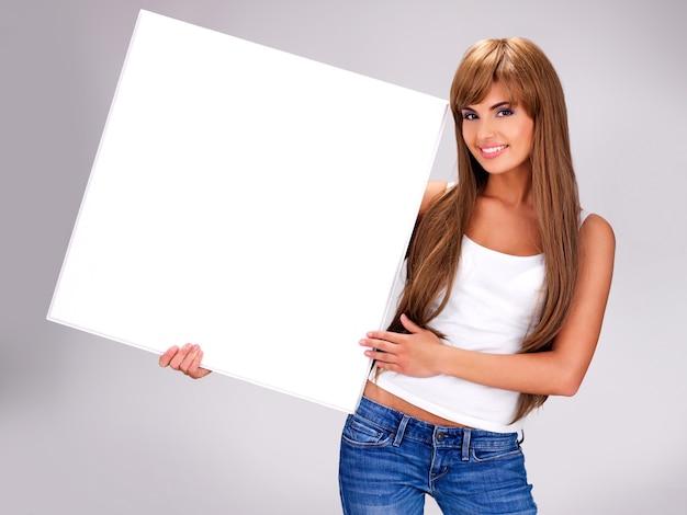 Mujer sonriente joven sostiene cartel grande blanco posando