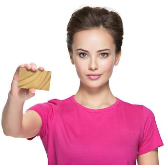 Mujer sonriente joven tiene tarjeta de crédito