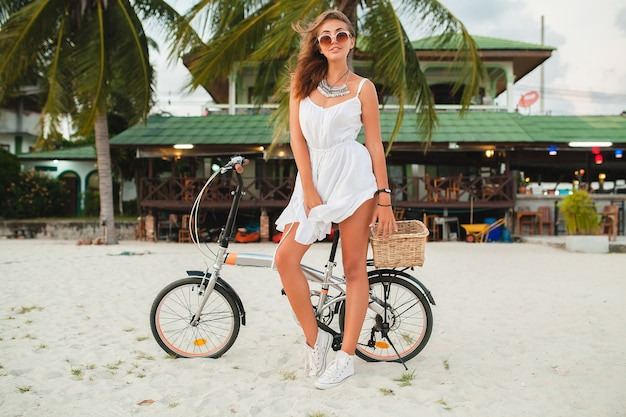 Mujer sonriente joven en vestido blanco a caballo en la playa tropical en gafas de sol de bicicleta viajando en vacaciones de verano en tailandia