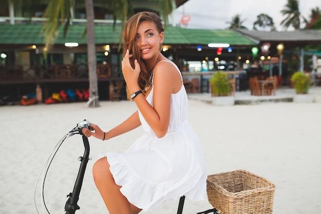 Mujer sonriente joven en vestido blanco caminando en la playa tropical con bicicleta viajando en vacaciones de verano en tailandia