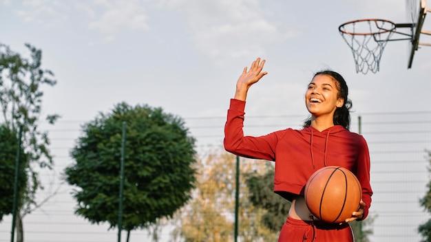 Mujer sonriente jugando baloncesto al aire libre con espacio de copia