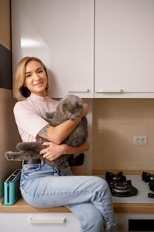 Mujer sonriente jugando con gato en la cocina de casa.