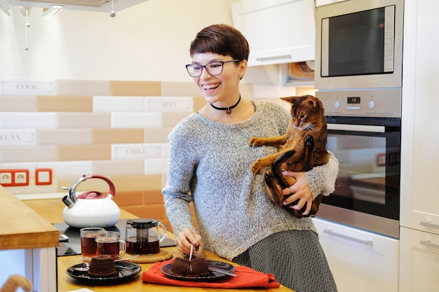 Mujer sonriente jugando con un gato jengibre y comiendo pastel en la cocina