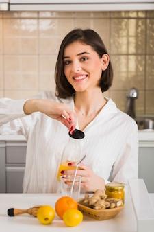 Mujer sonriente con jugo de naranja casero