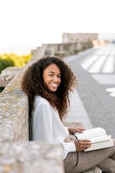 Mujer sonriente de lado que sostiene un libro abierto