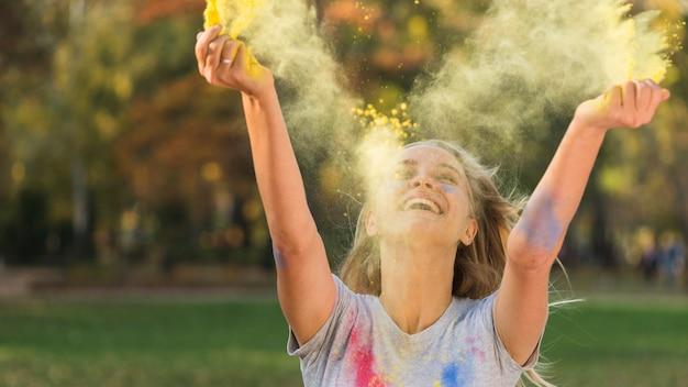 Mujer sonriente lanzando color en el aire