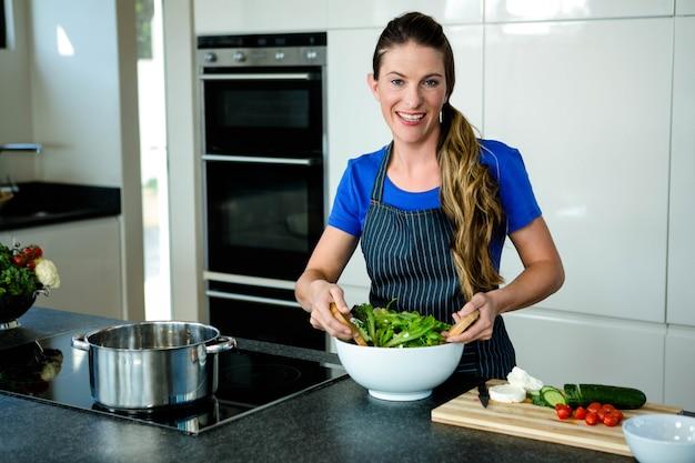 Mujer sonriente lanzando una ensalada en la cocina