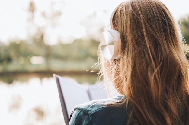 Mujer sonriente en lentes que lee el libro y que escucha la música con los auriculares en el parque al aire libre contra luz del sol, concepto de la forma de vida de la ciudad.