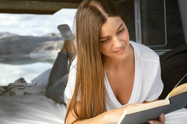 Mujer sonriente leyendo concepto de viaje por carretera