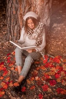 Mujer sonriente leyendo en el suelo