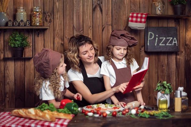 Mujer sonriente leyendo el libro de recetas con chicas en delantales y sombreros mientras cocina pizza en la acogedora cocina en casa juntos