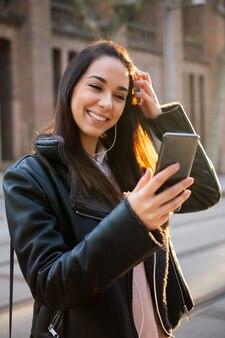 Mujer sonriente leyendo un mensaje en su teléfono