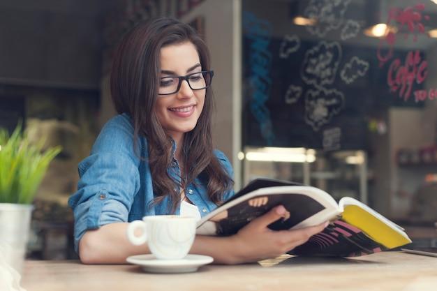 Mujer sonriente leyendo el periódico en el café