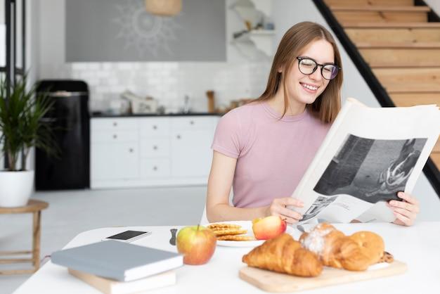 Mujer sonriente leyendo el periódico