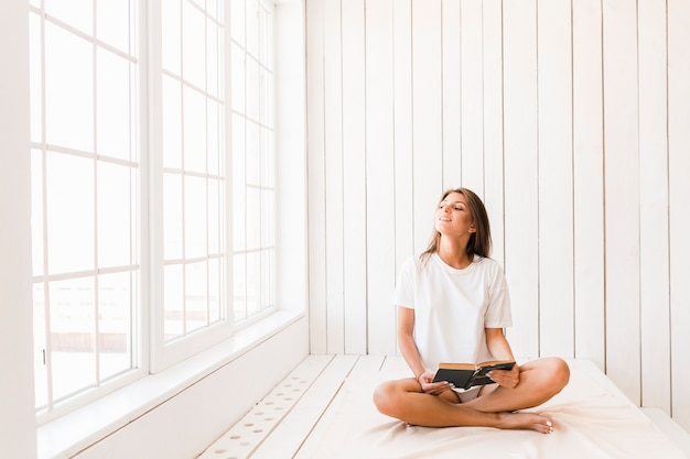 Mujer sonriente con libro disfrutando de la luz del sol