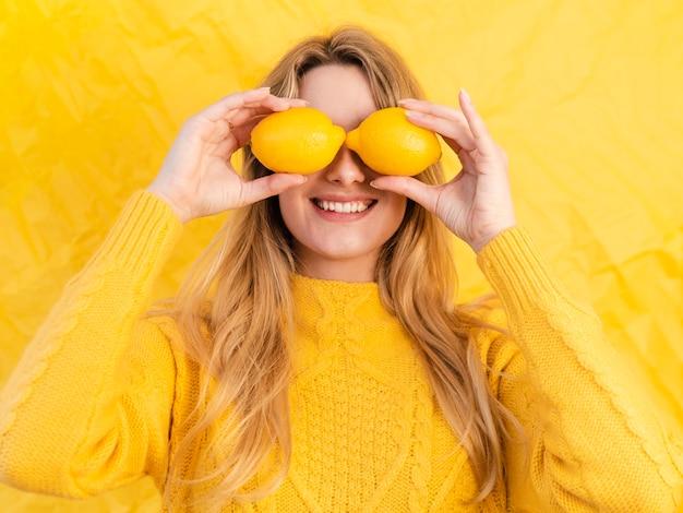 Mujer sonriente con limones