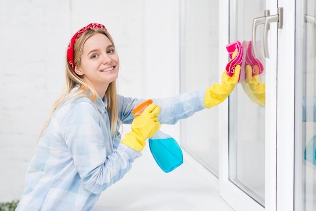 Mujer sonriente limpiando ventanas