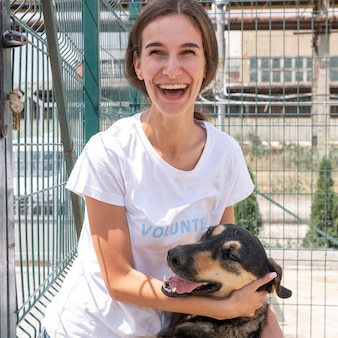 Mujer sonriente con lindo perro esperando ser adoptado por alguien