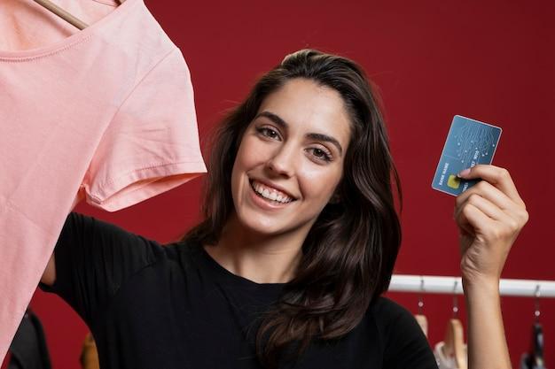 Mujer sonriente lista para comprar una camisa rosa