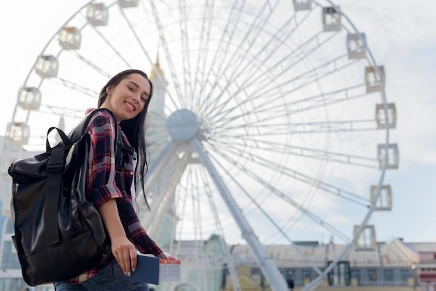 Mujer sonriente llevando mochila y sosteniendo pasaporte y boleto aéreo frente a la noria