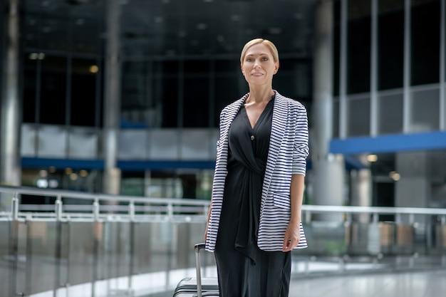 Mujer sonriente con maleta caminando en el aeropuerto