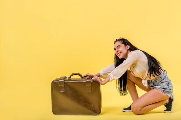 Mujer sonriente con maleta grande