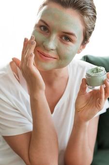Mujer sonriente con máscara facial sosteniendo un envase cosmético