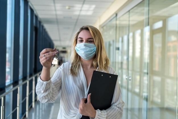 Mujer sonriente con máscara protectora con llaves de casa en el moderno centro de negocios. concepto de inmobiliaria y oficina.