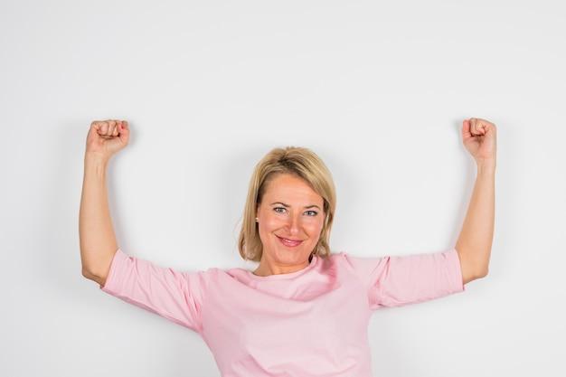 Mujer sonriente mayor con las manos levantadas en blusa color de rosa