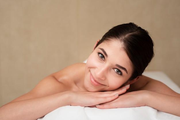 Mujer sonriente en mesa de masaje en el spa