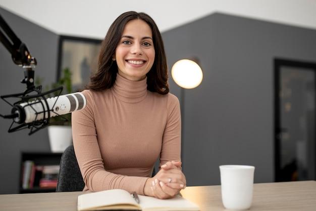Mujer sonriente con micrófono y café en un estudio de radio