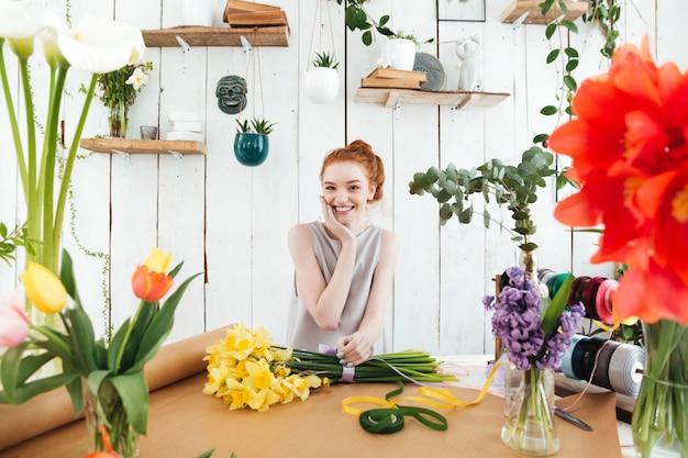 Mujer sonriente mientras trabaja con flores
