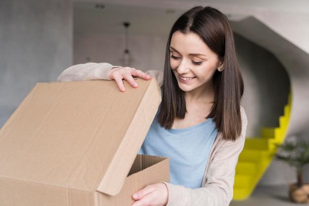 Mujer sonriente mirando en caja de cartón