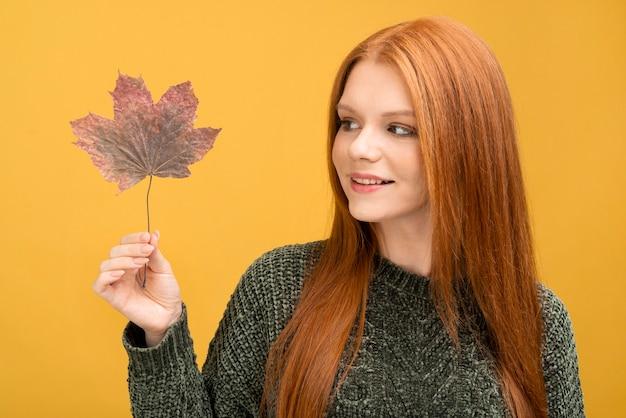 Mujer sonriente mirando la hoja de otoño