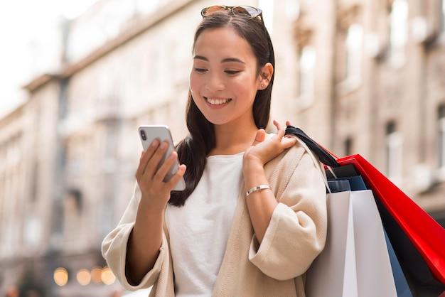 Mujer sonriente mirando smartphone al aire libre mientras sostiene bolsas de la compra.