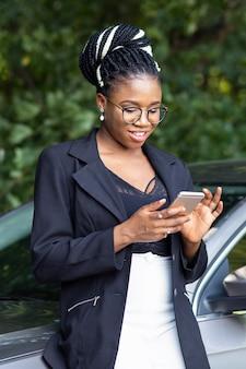 Mujer sonriente mirando smartphone mientras se inclina contra su coche