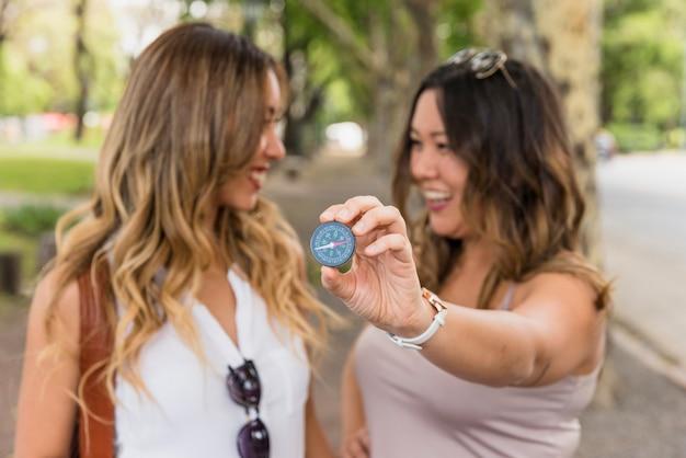 Mujer sonriente mirando a su amiga que muestra una brújula cerca de la cámara
