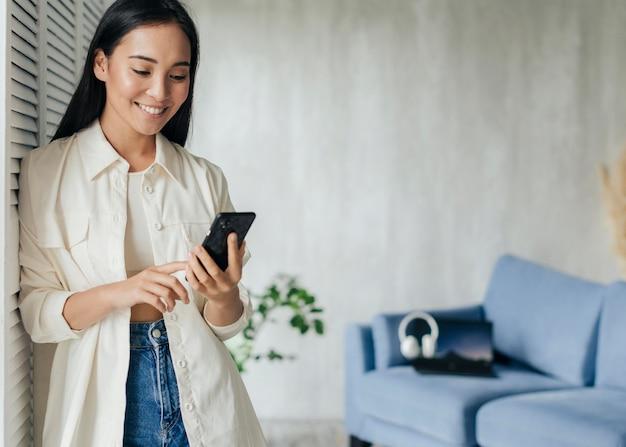 Mujer sonriente mirando el teléfono con espacio de copia