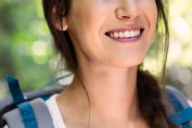 Mujer sonriente con mochila al aire libre en una aventura