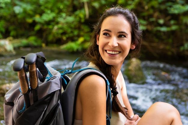 Mujer sonriente con mochila disfrutando de la naturaleza al aire libre