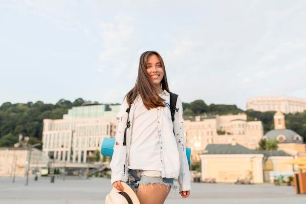 Mujer sonriente con mochila y sombrero posando mientras viaja