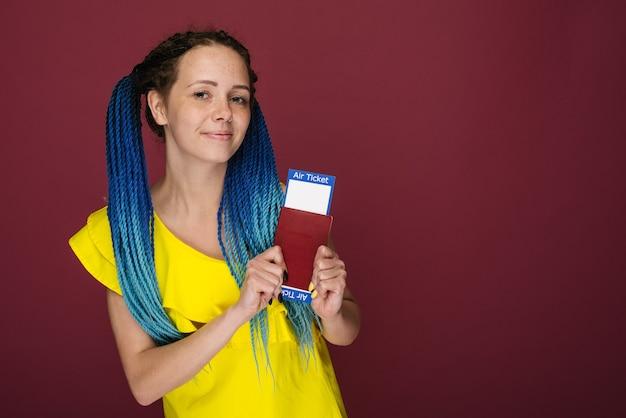 Una mujer sonriente de moda moderna en vestido amarillo con billetes de avión y un pasaporte en la mano