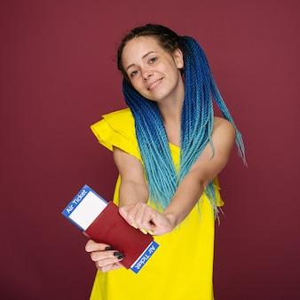 Una mujer sonriente de moda moderna en vestido amarillo con billetes de avión y un pasaporte en la mano.