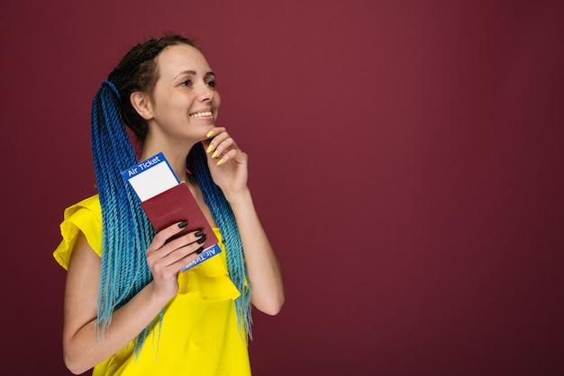 Una mujer sonriente de moda moderna en vestido amarillo con billetes de avión y pasaporte