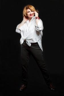 La mujer sonriente moderna con el pelo rojo en una camisa blanca está bailando. hermoso y feliz envejecimiento. fondo negro. altura completa. vertical.
