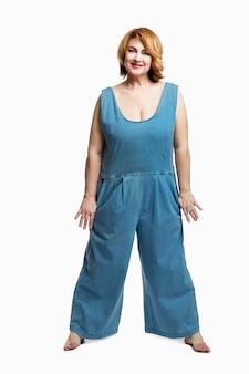 Mujer sonriente moderna con el pelo rojo en overoles de mezclilla descalzo. hermoso y feliz envejecimiento. . altura completa. vertical.